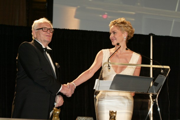 Master of Ceremonies Sharon Stone welcomes iconic fashion designer Pierre Cardin to the podium of the 2004 Gala